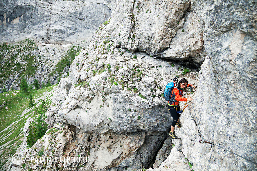 Woman climbing the Via Ferrata F. Gadotti above Val San Nicolo