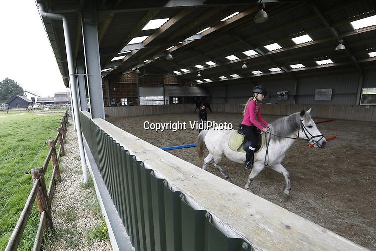 Foto: VidiPhoto<br /> <br /> OPHEUSDEN &ndash; Meisjes krijgen paardrijlessen bij stal &rsquo;t Nijland in Opheusden.