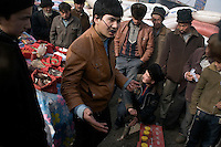 Uighur men crowd around a street vendor selling traditional Chinese medicine outside the Kashgar Sunday Animal Market outside Kashgar, Xinjiang, China.