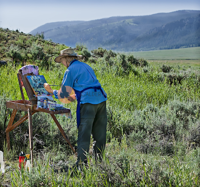 Senior female artist painting on an easel, outdoors in Yellowstone National Park