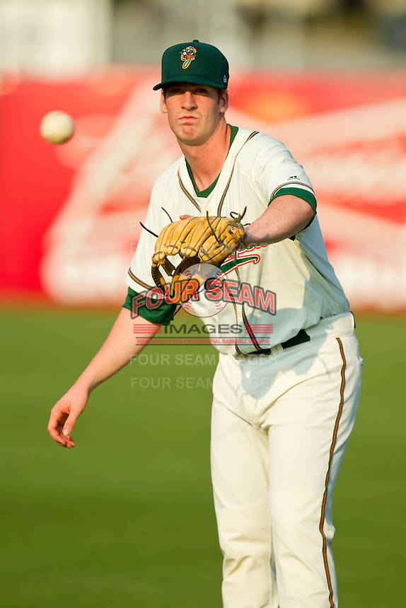 Colin Moran (14) of the Greensboro Grasshoppers warms up in the outfield prior to the game against the Charleston RiverDogs at NewBridge Bank Park on July 17, 2013 in Greensboro, North Carolina.  The Grasshoppers defeated the RiverDogs 4-3.  (Brian Westerholt/Four Seam Images)