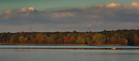 A fishing boat navigates it way across Hoover Reservoir as trees turn golden in the fall.<br />