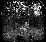 1998-Fat Mikey sits down in need of a rest after clearing an island in the Everglades for camping, fishing  and hunting with his family and friends. Access to the island is by airboat only. The Florida Everglades are a disappearing world. Overpopulation, the sugar and cattle industry, mismanagement of the land, droughts and bush fires are just a few of the problems the Florida Everglades are facing. Here Glen Wilsey driving his airboat. According to Glen the best thing about being a tour guide in the everglades is driving the airboats. Riding an airboat is fun but driving an airboat is an awesome feeling.