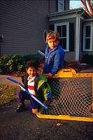 Two little boys posing with thei plastic hockey sticks in the driveway.