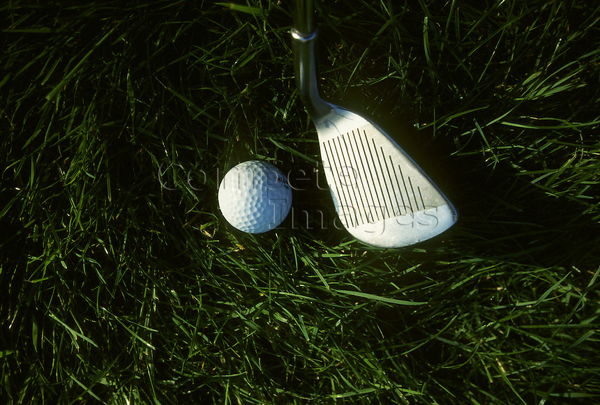Close up of a golf club and golf ball in rough grass