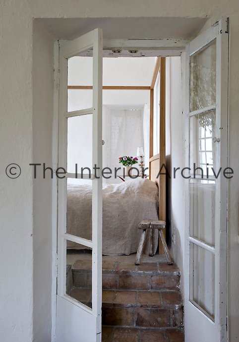 View into the bedroom with a contemporary wooden four-poster bed covered with a linen bed cover