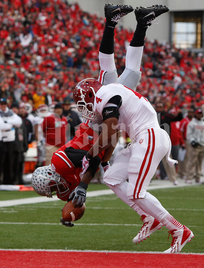 Ohio State Buckeyes quarterback Braxton Miller (5) flips into the endzone for a touchdown as he is hit by Indiana Hoosiers linebacker Forisse Hardin (4) making the score 21-0 in the second quarter during Saturday's NCAA Division I football game at Ohio Stadium in Columbus on November 23, 2013. (Barbara J. Perenic/The Columbus Dispatch)