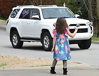 Ansley Sandlin (right), a kindergarten student at Vandergriff Elementary School, waves Monday, March 23, 2020, to teachers and faculty in a parade as they drive through the area neighborhood. Students and family members were encouraged to come out and wave from a distance. The teachers were showing their support for the students and expressing how much they miss them. Check out nwaonline.com/2003224Daily/ and nwadg.com/photos for a photo gallery.<br /> (NWA Democrat-Gazette/David Gottschalk)