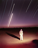 SAUDI ARABIA, Najran, The Empty Quarter, portrait of a man standing on sand dunes in The Empty Quarter with stars in the sky