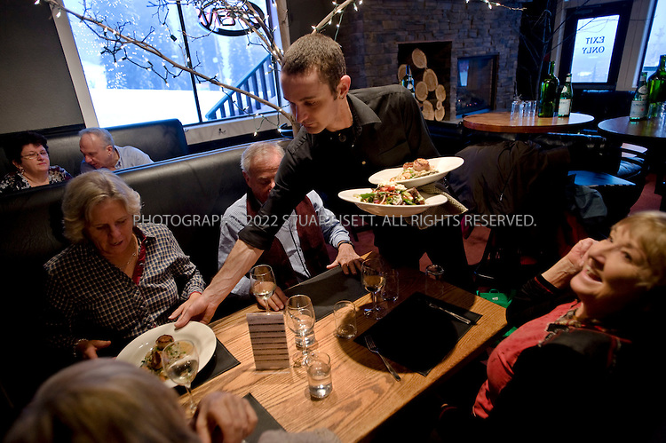 3/10/2008--SIlver Star Mountain, British Columbia, Canada..Dinner at the The Den Bistro and Bar in the village at the SIlver Star Mountain Resort. Silver Star Mountain Resort, British Columbia with most of its buildings designed in the Victorian Era style. The mile-high resort is surrounded by British Columbia provincial park lands and its small pedestrian-only village nestles mid-mountain. Silver Star Mountain lies in the interior of British Columbia amidst mountain ranges, valleys and lakes..In winter, the mountain resort offers 115 ski and snowboard trails including thirteen double black diamond runs for the more adventurous or teenaged members of the family. The summer hosts a smaller crowd, with activities for the mountain biker, nature lover, and golf is nearby...In the last six years, Silver Star has begun to transform from sleepy provincial ski area to world class boutique family resort. In 2002, the Schumann family bought the resort, and have invested $25M in five new chair lifts and other infrastructure. Now, builders are using higher quality fit and finish on new luxury condominium complexes, home prices are going up, and some winter weekends are selling out...©2008 Stuart Isett. All rights reserved