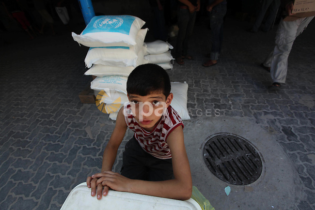 A Palestinian boy sits next to bags of flour stored at a distribution centre of the United Nations Relief and Works Agency (UNRWA) in Gaza City on August 11, 2014. An Israeli delegation arrived in Cairo for indirect negotiations with Palestinians on a durable truce in Gaza, Egypt and Israeli officials said. Photo by Ashraf Amra