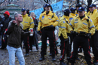 November 23, 2011, Toronto Police deployed in significant numbers during the predawn hours this morning, beginning the process of evicting the Occupy Toronto tent camp from St. James Park.  Here an angry protester is seen amongst ten officers.