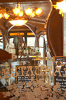 Detail of a glass partition partitioning facetted and engraved etching text Restaurant and a bouquet of flowers. In the background mirrors and the menu, the bar with bottles on the shelf The Bistrot du Peintre is an old fashioned Paris café cafe bar restaurant of art nouveau design with polished brass, mirrors and old signs