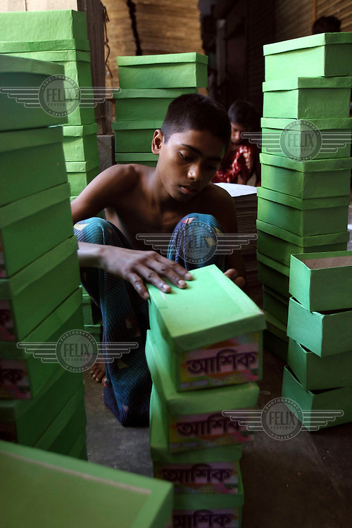 14-year-old Kamal works in a factory that makes shoe boxes.