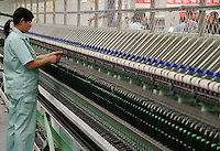 A worker mans a textile machine at the ShanghaiTex 2005, a textile industry exhibition  in Shanghai, China. China is currently engaged in heated trade disputes with both the European Union and then United States over its exports of textiles to these two areas..05 Jun 2005