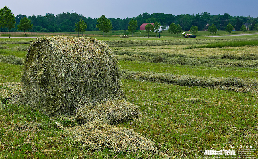 Farmers work the first hay cut of the season before rain moves across the field