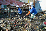 Maryglen Roa (left) and Jeanette Ayo clean up debris in Tacloban, a city in the Philippines province of Leyte that was hit hard by Typhoon Haiyan in November 2013. The storm was known locally as Yolanda. They are participants in a United Nations funded cash for work program.