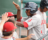 Outfielder Felix Sanchez (34) of the Greenville Drive is congratulated in the dugout after scoring a run in a game against the Charleston RiverDogs on July 31, 2011, at Fluor Field at the West End in Greenville, South Carolina. The Drive wore throwback jerseys honoring the textile mill baseball teams. (Tom Priddy/Four Seam Images)