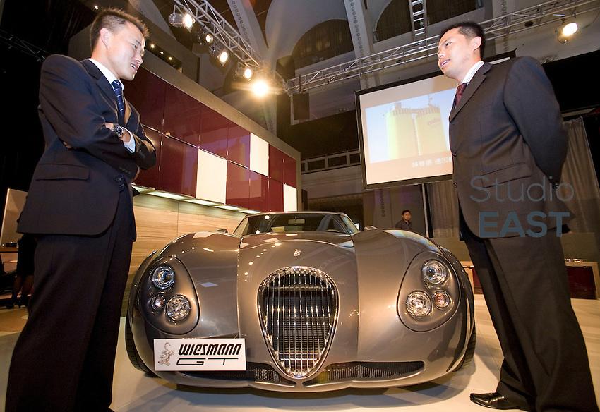Staff stand by a German built Weissman GT sports car valued at 300,000 USD at a luxury goods fair in Shanghai on October 10, 2008. The three day event 'The Fair' that was formerly called the 'Millionaires Fair' hopes to attract over 15 000 wealthy Chinese to view the range of luxury cars and goods on display. Photo by Lucas Schifres/Pictobank