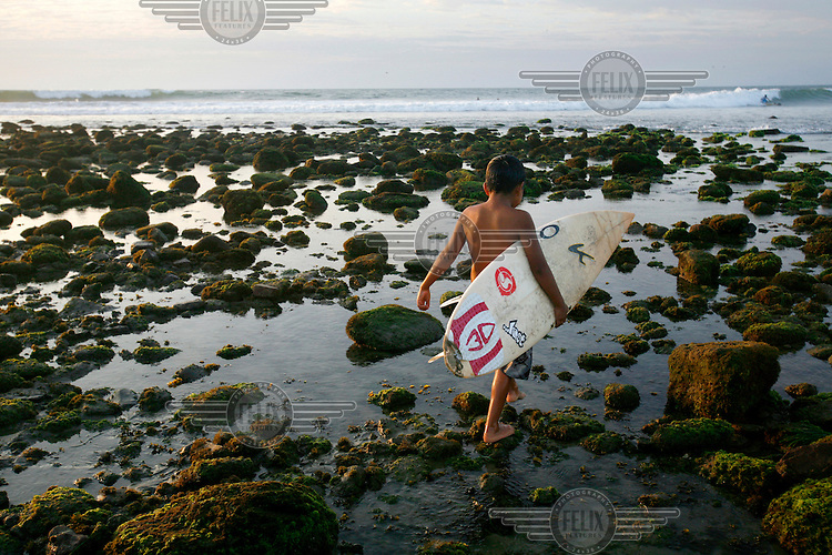 A young boy, with a surfboard, walks gingerly across a barrier of rocks between the beach and the surf. Mancora was once a quiet fishing village but due to its world class surf break it has become a magnet for surfers from around the world while many of the younger villagers have adopted a surfing lifestyle.