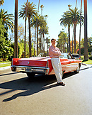 USA, California, Beverly Hills, a man stands in the street leaning on his red convertible Cadillac