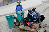 A woman of the ethnic Bouyei Tribe washes laundry at a public tap at Wangmo County in China's southwestern Guizhou Province, April 2019.