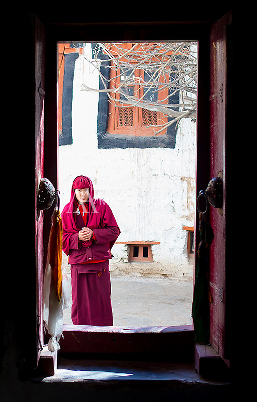 A Buddhist monk pauses at a doorway in the Hemis Monastery.