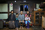 A poor farmer and his family living in a traditional dwelling finding it hard to make ends meet. Punakha, Bhutan..Bhutan the country that prides itself on the development of 'Gross National Happiness' rather than GNP. This attitude pervades education, government, proclamations by royalty and politicians alike, and in the daily life of Bhutanese people. Strong adherence and respect for a royal family and Buddhism, mean the people generally follow what they are told and taught. There are of course contradictions between the modern and tradional world more often seen in urban rather than rural contexts. Phallic images of huge penises adorn the traditional homes, surrounded by animal spirits; Gross National Penis. Slow development, and fending off the modern world, television only introduced ten years ago, the lack of intrusive tourism, as tourists need to pay a daily minimum entry of $250, ecotourism for the rich, leaves a relatively unworldly populace, but with very high literacy, good health service and payments to peasants to not kill wild animals, or misuse forest, enables sustainable development and protects the country's natural heritage. Whilst various hydro-electric schemes, cash crops including apples, pull in import revenue, and Bhutan is helped with aid from the international community. Its population is only a meagre 700,000. Indian and Nepalese workers carry out the menial road and construction work.