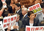 July 15, 2015, Tokyo, Japan - Opposition lawmakers holding protest signs surround the chairman as they try to obstruct proceedings during a vote on the government-sponsored security related bills in a Diet lower house special committee on national security in Tokyo on Wednesday, July 15, 2015. The committee voted to approve the bills with the support of the ruling Liberal Democratic Party and its junior coalition partner Komeito. The bills will be put to a vote in a Diet plenary session as early as July 16, after which it will be sent to the upper house. The bills, when enacted, will allow Japan to exercise its right to collective self-defense.  (Photo by Natsuki Sakai/AFLO) AYF -mis-