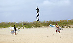 Ettienne Bacciche, left, and Hadrian Corning, visiting the Outer Banks from Montreal, carry their surf boards onto the beach near the Cape Hatteras Lighthouse.