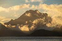 Himmeltindan mountain peak circled by clouds, Vestvågøy, Lofoten Islands, Norway