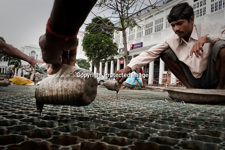 Construction workers are seen working to finish the beautification process in Connaught Place in New Delhi, India.