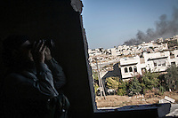 In this Tuesday, Oct. 08, 2013 photo, smoke rises from a burning tank as an opposition fighter commander watchs over his enemy position at the frontline in Maraat Al-Nouman in the Idlib province countryside of Syria. (AP/Photo)