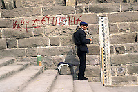 A man sits in front of a stick that is used to measure the height of flood water in the city of Chongqing. Chongqing will be a deep water port at the end of the massive Three Gorges Dam Scheme when it is completed in 2007.