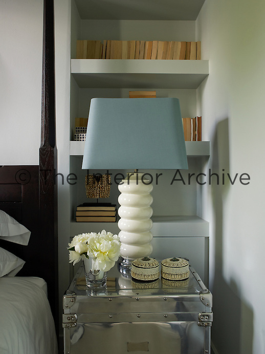 A stainless-steel trunk topped with a ceramic lamp and a vase of flowers serves as a bedside table