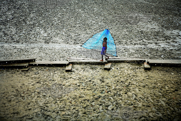 A small child walks on planks put there to enable people to travel across the mud. Thousands of people were displaced in Shyamnagar Upazila, Satkhira district after Cyclone Aila struck Bangladesh on 25/05/2009, triggering tidal surges and floods..