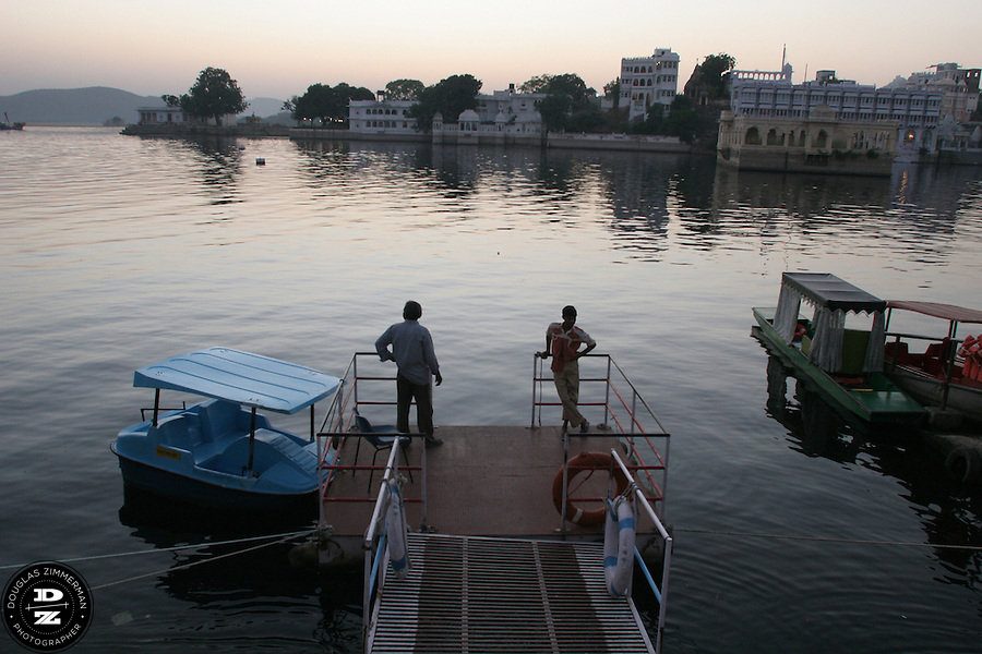"""Two paddle boat vendors watch the sunset at Lal Ghat at Pichola Lake in Udaipur, Rajasthan, India.  Udaipur is located in a valley surrounded by the Aravalli hills, and at its center is the Pichola Lake.  The scenic city has been described as """"the most romantic spot on the continent of India"""" (by Colonel James Tod).  Photograph by Douglas ZImmerman"""