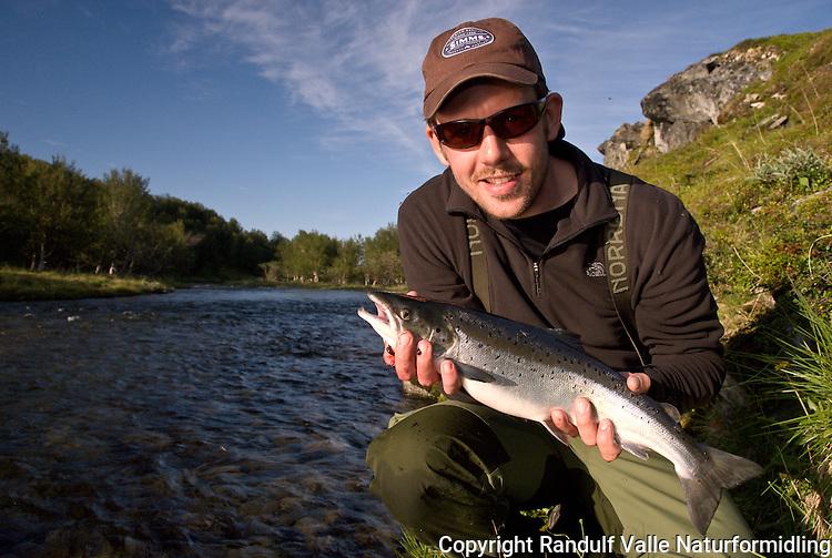 Mann holder smålaks. --- Man holding small salmon.