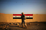 A Marine passes from 2nd BN 5th Marines walks past a newly painted Iraqi flag on a wall during a patrol through central Ramadi on Tuesday May 10, 2007. In recent weeks and months, Ramadi, the provincial capital of the turbulent al-Anbar province has turned from one of the most deadly places in Iraq into an island of relative stability as tribal leaders there have split from the insurgency after years of killings and intimidation.