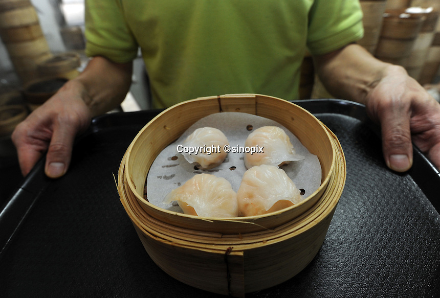 Mak Pui Gor, 50, of Tim Ho Wan the cheapest Michelin starred restaurant in the world, holds steamed shrimp dumpling in Hong Kong..17-Jul-11..Photo by Richard Jones......