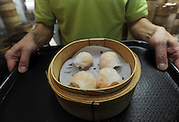 Mak Pui Gor, 50, of Tim Ho Wan the cheapest Michelin starred restaurant in the world, holds steamed shrimp dumpling in Hong Kong..17-Jul-11..Photo by Richard Jones......