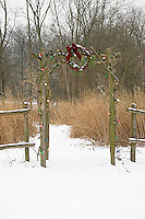 63821-19403 Rustic fence and arbor with holiday wreath & lights near prairie in winter, Marion Co.  IL