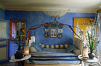 In this bedroom an antique wrought-iron bed, striped bed coverings and walls distempered a soft blue have created a rustic Moroccan feel