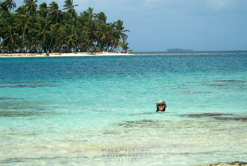 Young woman in blue bikini and cowboy hat enjoying shoreline, Comarca De Kuna Yala, San Blas Islands, Panama