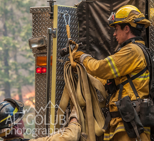 Colorado firefighters hang hoses before moving fire truck on Harden Flat Road near Highway 120.