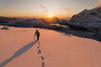Female hiker at dawn on winter hike of Kollfjellet, Flakstadøy, Lofoten Islands, Norway