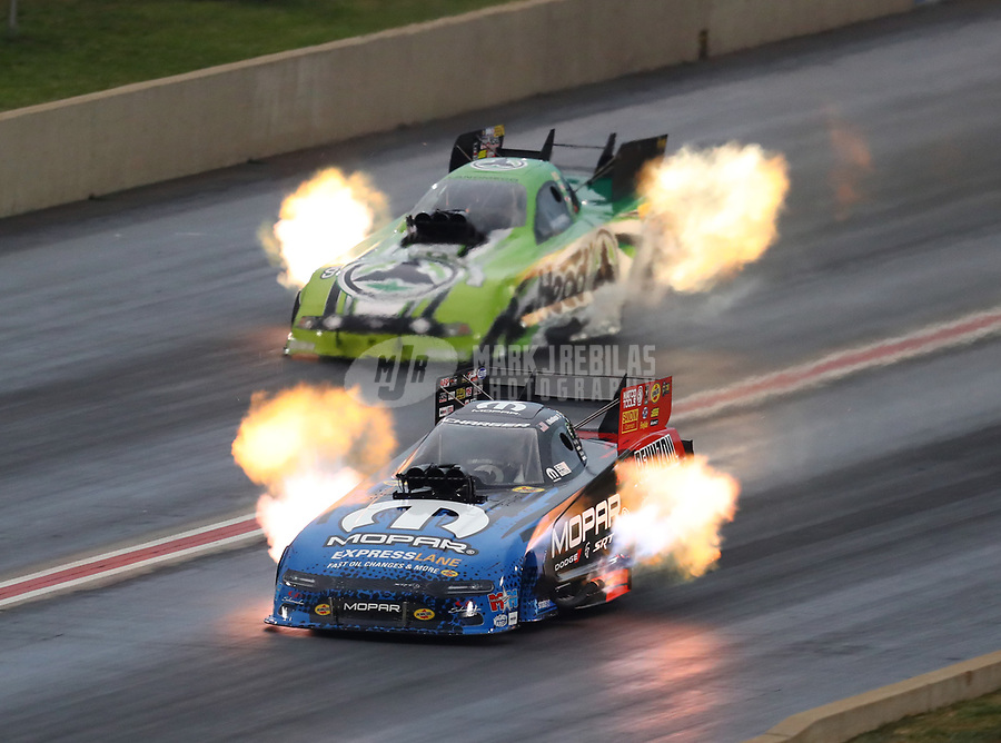 Jul 21, 2018; Morrison, CO, USA; NHRA funny car driver Matt Hagan (near) races alongside Jonnie Lindberg during qualifying for the Mile High Nationals at Bandimere Speedway. Mandatory Credit: Mark J. Rebilas-USA TODAY Sports