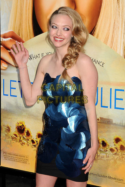 """AMANDA SEYFRIED.Attending """"Letters To Juliet"""" Los Angeles Premiere held at Grauman's Chinese Theatre, Hollywood, California , USA, .11th May 2010..arrivals half length  side fishtail plaid braid strapless blue dress black applique textured texture pleated fans hand waving smiling white rosettes  .CAP/ADM/BP.©Byron Purvis/AdMedia/Capital Pictures."""