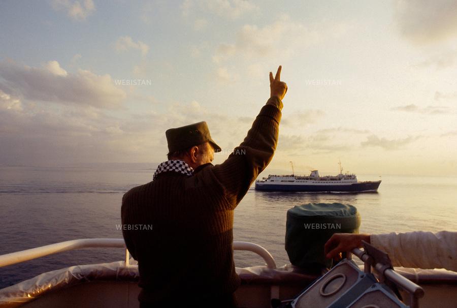 """1983. Suez Canal. During the Lebanese War (1975-1990), Yasser Arafat (1929-2004), chairman of the PLO, makes the""""V"""" of victory on board of the Odysseus Elytis boat, at his entrance in the Suez Canal, during his evacuation by the international community. Canal de Suez. Pendant la Guerre du Liban (1975-1990), Yasser Arafat (1929-2004), le chef de l'OLP, fait le """"V"""" de la victoire à bord du bateau Odysseus Elytis, lors de son entrée dans le Canal de Suez, pendant son évacuation par la communauté internationale."""