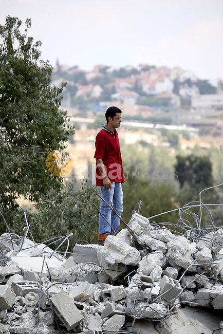A Palestinian youth stands on the rubble of a house in the West Bank village of Lubban al-Gharbia on July 21, 2010 after Israeli forces demolished two houses and four shops that were built without the army's permit near a road leading to the nearby Jewish settlement of Beit Arieh. Photo by Eyad Jadallah